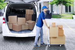 Italian man courier pushing a trolley. Picture of Italian man courier pushing trolley while delivering packages. Shot at outdoor Stock Image