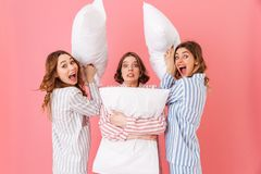 Picture of joyous women 20s wearing colorful striped pyjamas hav. Ing fun and fooling around at slumber party isolated over pink background Royalty Free Stock Image