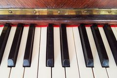 Picture of keys from an old fancy piano, with brown wood. Royalty Free Stock Photography