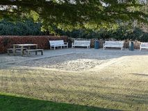 Large sandbox with several white benches, picnic table and waste bins stock images