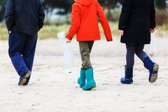 Family walks in autumn at the beach. Picture of the legs of a family walking in autumn at the beach Stock Photos