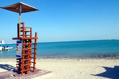 Picture of a lifeguard chair on an emply beach and overcast blue sky on sunny day. Picture of a lifeguard chair on an emply beach, calm sea and overcast blue sky royalty free stock photos