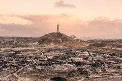A lighthouse stands alone on a hill in iceland. This is a picture of a lighthouse standing alone on a hill in iceland stock photo