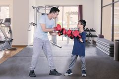 Child ready to fight with his father in gym center royalty free stock photo