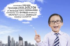 Little boy thinking his future jobs. Picture of little boy wearing glasses while thinking his future jobs on a cloud bubble Royalty Free Stock Photography