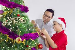 Little boy and his father decorating Christmas tree. Picture of a little boy wearing a Santa hat while decorating a Christmas tree with his father in the studio royalty free stock image