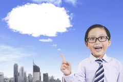 Little businessman with empty cloud speech bubble. Picture of little businessman getting an inspiration while pointing empty cloud speech bubble in the sky Stock Photo