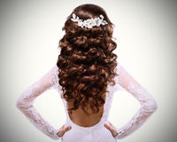 Picture of long curly brown hair.brunette girl in white wedding dress with a low-cut back Stock Image