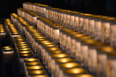 Picture of a lot of burning candles in a row. Dramatic picture of a lot of burning candles in a row royalty free stock image
