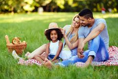 Picture of lovely couple with their daughter having picnic. In nature Royalty Free Stock Images