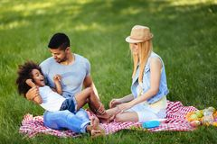 Picture of lovely couple with their daughter having picnic Stock Photos