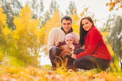 Picture of lovely family in autumn park, young parents with nice adorable kids playing outdoors, five cheerful person have fun on Royalty Free Stock Images
