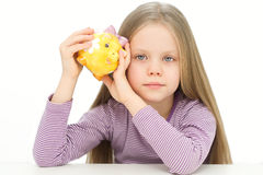 Picture of lovely small girl with piggy bank. Near her head Stock Photos