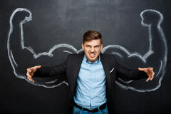 Picture of  mad man with  fake muscle arms. Picture of  angry, mad suited business  man with  fake muscle arms over blackboard. hand whrite Stock Photos
