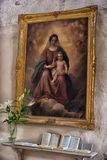 picture of the Madonna and Child on the wall of the church and prayer underneath Stock Images