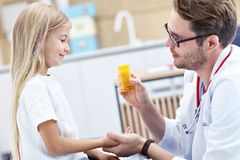 Male doctor giving pills to little girl stock image
