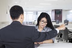 Male manager firing his employee. Picture of a male manager firing his employee while pointing out and sitting in the office Royalty Free Stock Images