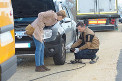 Picture male mechanic replacing clients car tire Royalty Free Stock Photo