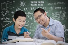Male teacher helping his student to count. Picture of male teacher helping his student to count while sitting in the classroom with scribbles on the chalkboard royalty free stock photo