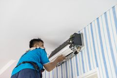 Male technician repairing an air conditioner. Picture of male technician repairing an air conditioner indoor. Shot at home Stock Photo