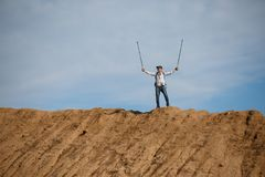 Picture of male tourist from afar with hands up with sticks for walking on hill stock photos
