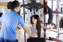 Trainer helping girl to exercise with weight machine. Picture of male trainer helping pretty girl to exercise with weight machine. Shot in the fitness center Royalty Free Stock Photo