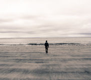 Picture of a man from behind walking on a beach in Scotland (UK). Polaroid Effect Stock Photos