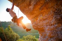 Picture of man clambering over rock. Sunlight effect stock images
