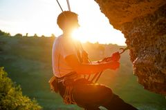 Picture of man clambering over rock. Sunlight effect stock photos
