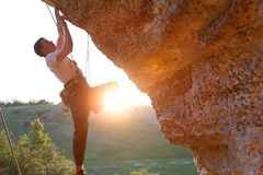 Picture of man clambering over rock. Sunlight effect stock photo