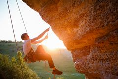 Picture of man clambering over rock. Sunlight effect royalty free stock photo