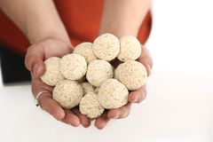 Picture of man hand is holding many cholai ke ladoo. Isolated on the white background stock photo