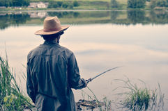 Picture of man having good time & fun fishing on bank on peaceful water outdoors copy space background Stock Photography