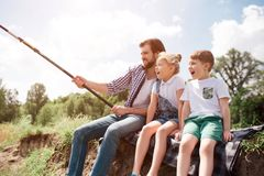 A picture of man and his children sitting together on the river shore. Guy is fishing while his kids are watching on it. A picture of men and his children stock image