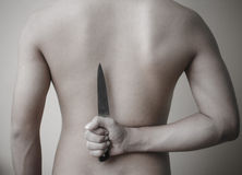 Picture a man holding a  knife behind his back Royalty Free Stock Photo