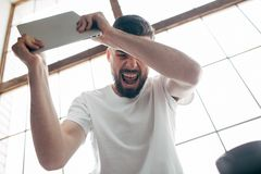 Guy at home. A picture of man that is insane. He holds a laptop in his hands and screaming. He is going to crush it. This guy is very mad and can`t calm down Stock Image