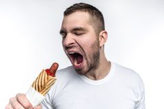 A picture of man that likes oily fast food. On this picture he wants to bite a big piece from fat hot dog. Man looks. Weird but brutal. Isolated on white royalty free stock photography