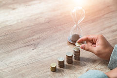 Picture of man putting stack of coins into one row Stock Image