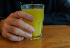 Hand of man wearing dark blue shirt, holding glass of juice stock image