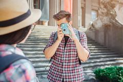 Picture of man standing and taking picture of young woman through camera. He is concentrated. Female tourist look at stock photos