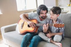 A picture of man teaching his son how to play on the guitar. He holds it and looks at fingers. Boy is sitting very close. A picture of men teaching his son how royalty free stock images
