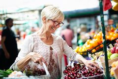 Picture of mature woman at marketplace buying vegetables. Picture of senior happy woman at marketplace buying vegetables and fruits royalty free stock photography