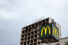 Mc Donald`s logo with its iconic M in front of a half destroyed building in downtown Belgrade. Picture of a Mc Donalds sign with its iconic M logo in front of a Stock Images