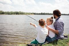 A picture of man and his children sitting together on the river shore. Guy is fishing while his kids are watching on it. A picture of men and his children royalty free stock images