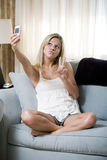 Picture Messaging. Young teenage girl snapping a picture of herself on camera phone royalty free stock photo