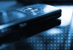Picture of a mobile phone. Blue toned picture of a mobile phone (shallow DoF, focused on round central button Stock Images