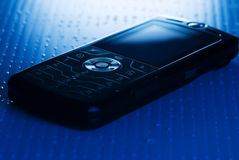 Picture of a mobile phone. Blue toned picture of a mobile phone (shallow DoF, focused on round central button Stock Photography