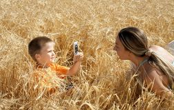 Picture of mom. Lovely kid picturing mom with cell phone Stock Images