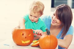 Mother and son preparing jack-o-lantern for Halloween. Picture of mother and son preparing jack-o-lantern for Halloween Royalty Free Stock Photo