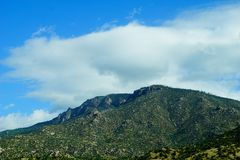 Mountain peak against the sky. A picture of a mountain peak against the clouds and blue sky Royalty Free Stock Images